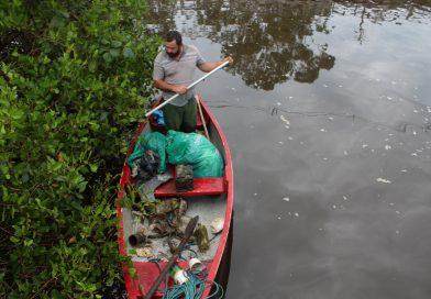 Pescador retira lixo das margens do rio. No meio do material recolhido havia uma bateria de carro