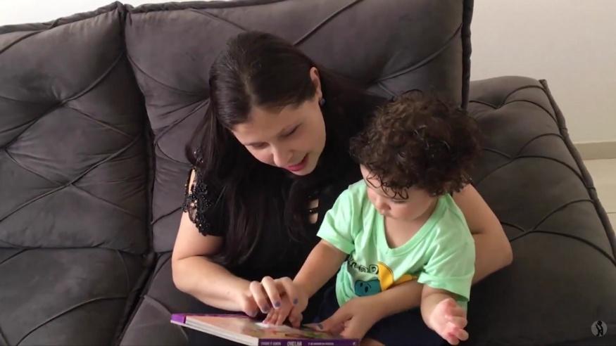Gustavo, um bebê de cabelo cacheado castanho escuro, senta no colo da mãe, Luciana, tocando numa das texturas do livro que ela segura. Luciana é branca, tem cabelo castanho escuro liso e comprido, e está contando a Gustavo a história que o livro narra.
