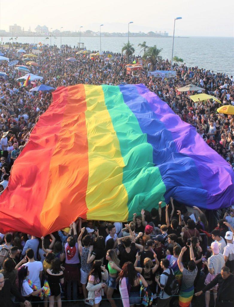 Uma multidão ergue uma bandeira com as cores o arco-íris gigante