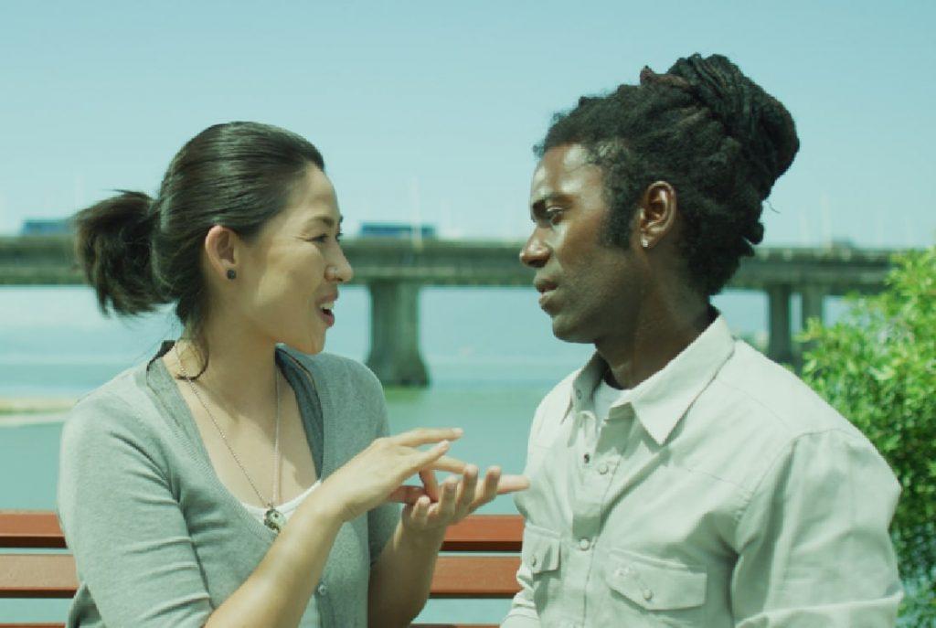 Uma mulher branca de descendência asiática conversa com um homem negro em um banco de madeira