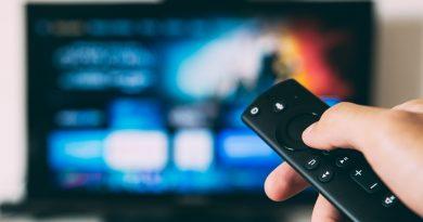 Uma mão segura um controle remoto apontado em direção a uma TV